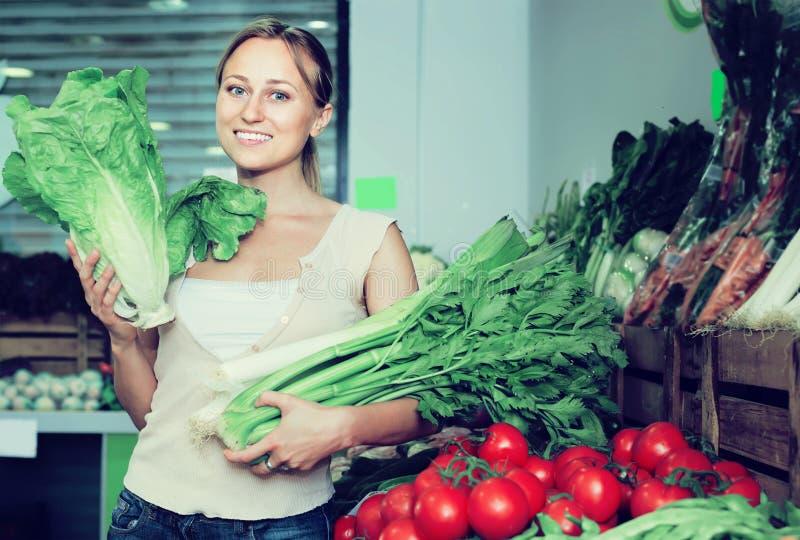 Молодой женский клиент держа свежие сельдерей и лук-порей стоковая фотография rf