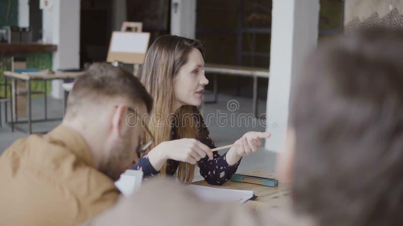 Молодой женский менеджер давая направление к ее команде Многонациональная группа людей на планировании утра в офисе просторной кв стоковые фото