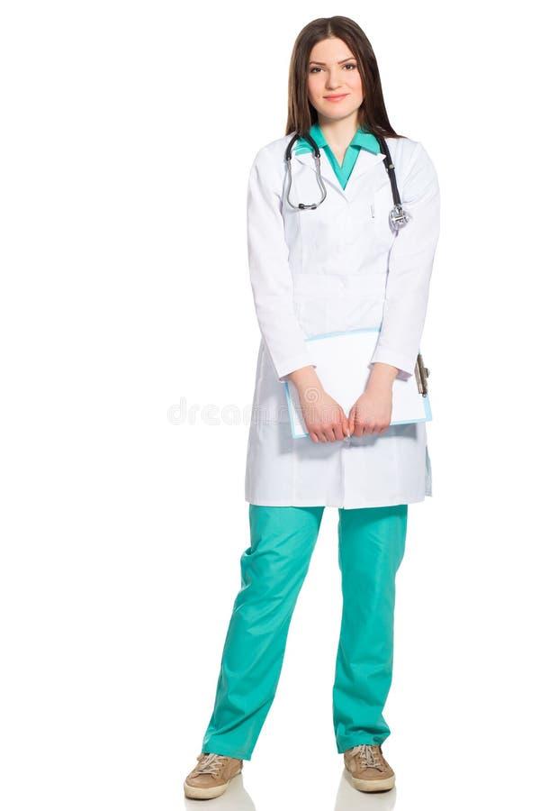 Молодой женский доктор в форме с доской сзажимом для бумаги и стетоскопом стоковые фото