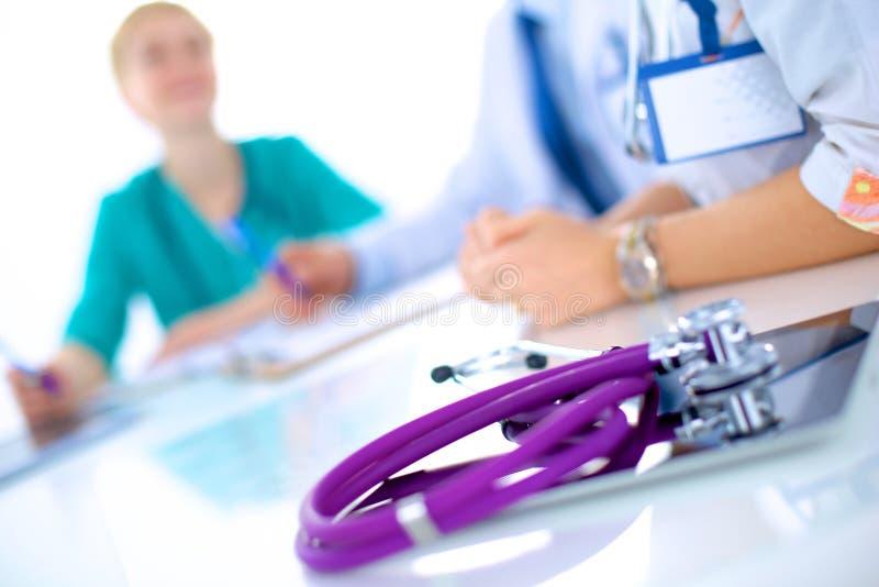 Молодой женский доктор сидя на столе стоковое фото