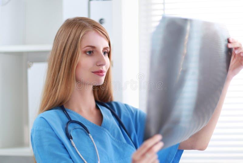 Молодой женский доктор смотря изображение рентгеновского снимка стоковое изображение