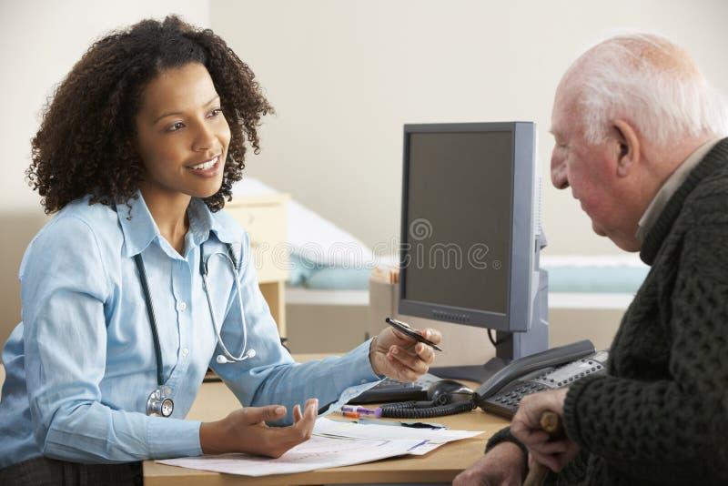 Молодой женский доктор с старшим мужским пациентом стоковая фотография