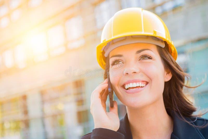 Молодой женский подрядчик нося трудную шляпу на месте используя телефон стоковое фото