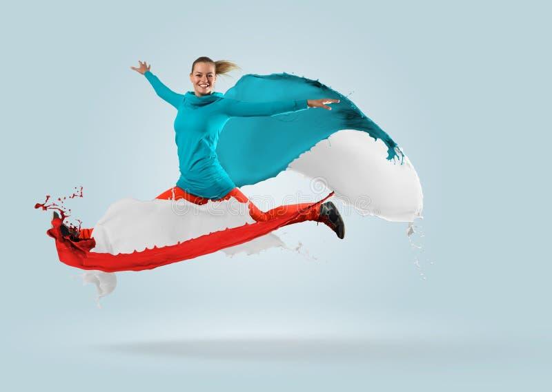 Молодой женский танцор скача с выплеском краски стоковое изображение rf