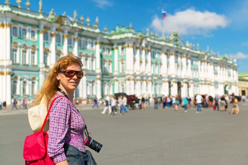 Молодой женский турист проходит Зимний дворец в Святом Petersbur стоковые изображения