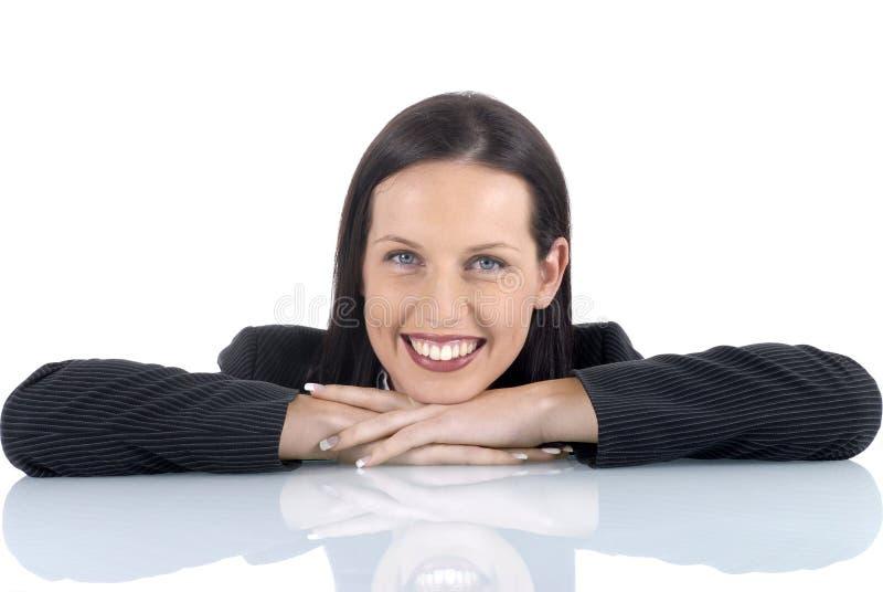 Молодой женский юрист-профессионал юриста ослабляя с улыбкой, оружиями сложил на столе стоковые фотографии rf