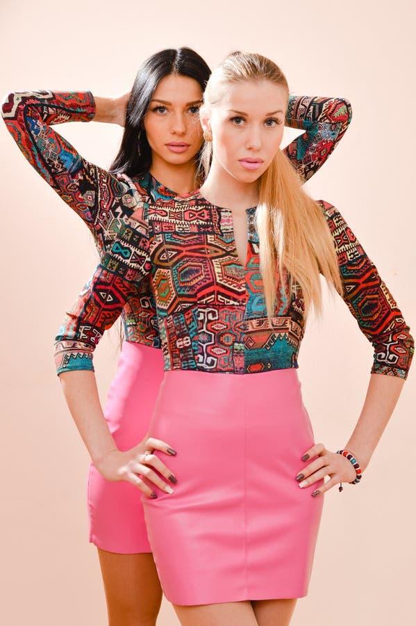 2 молодой женщины блондинка & брюнет серьезных сестер красивых нося такие же яркие платья & смотря камеру на белом backgr стоковое фото
