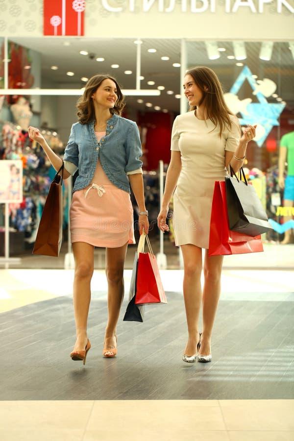 2 молодой женщины идя с покупками на магазине стоковая фотография rf