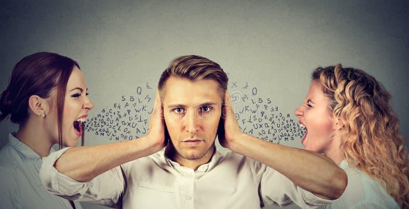 2 молодой женщины кричащей на спокойном человеке покрывая его уши при руки игнорируя их стоковые изображения rf