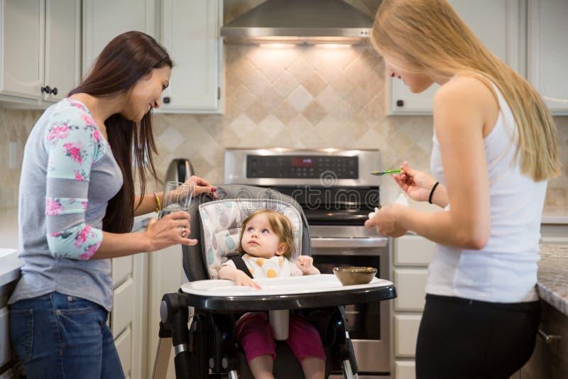 2 молодой женщины подавая маленькая девочка в высоком стульчике стоковое фото