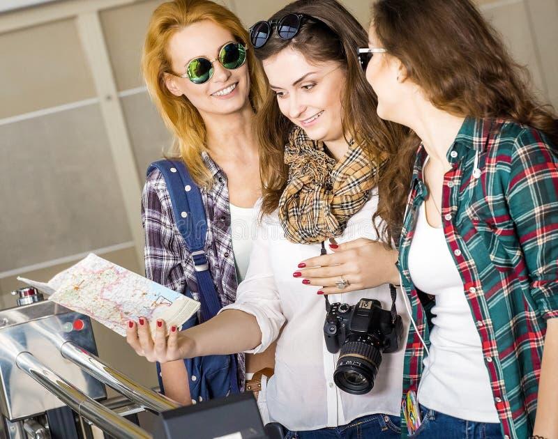 3 молодой женщины смотря в карте на вокзале или авиапорте европейцы Собранный в экскурсии друзья 3 стоковые изображения rf