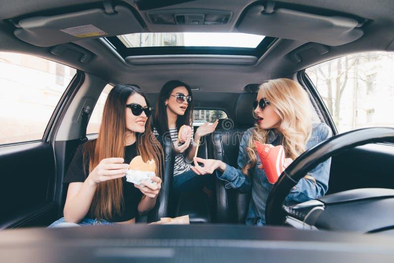 3 молодой женщины управляют автомобилем, говоря одином другого и едой фаст-фуда в автомобиле в заторе движения стоковые изображения rf