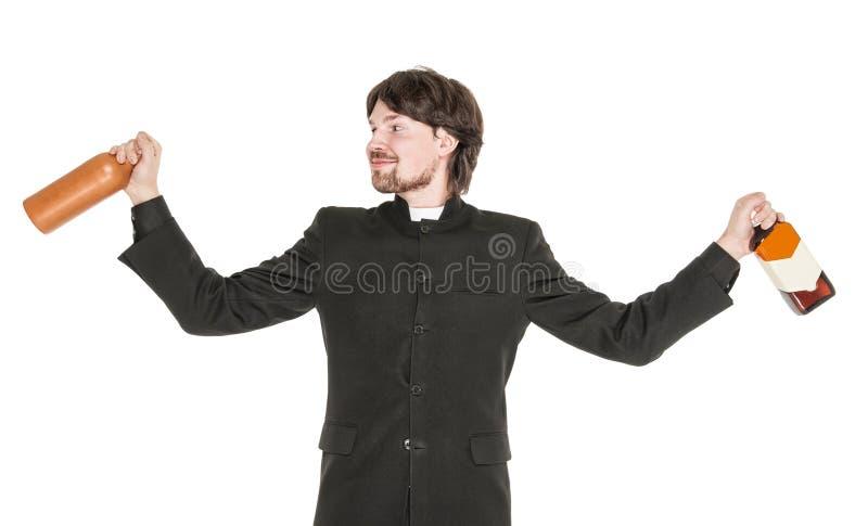 Молодой жизнерадостный священник при изолированная бутылка спирта стоковая фотография