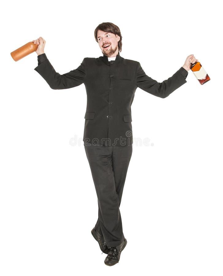 Молодой жизнерадостный священник при изолированная бутылка спирта стоковое фото