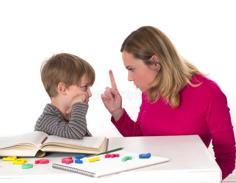 Молодой зрачок не хочет выучить, он противостоит его матери которая угрожает его стоковые изображения rf