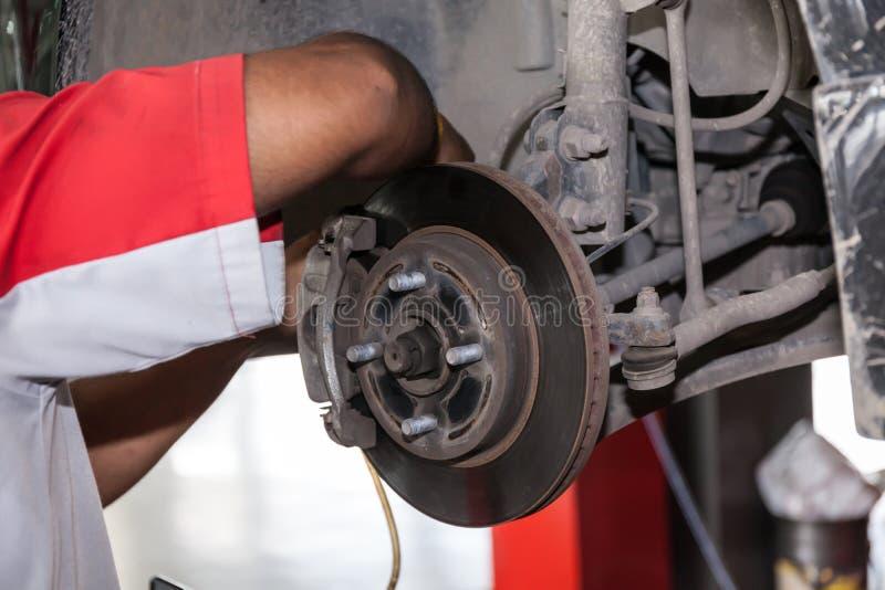 Молодой диск тормоза отладки техника в гараже автомобиля стоковые изображения rf