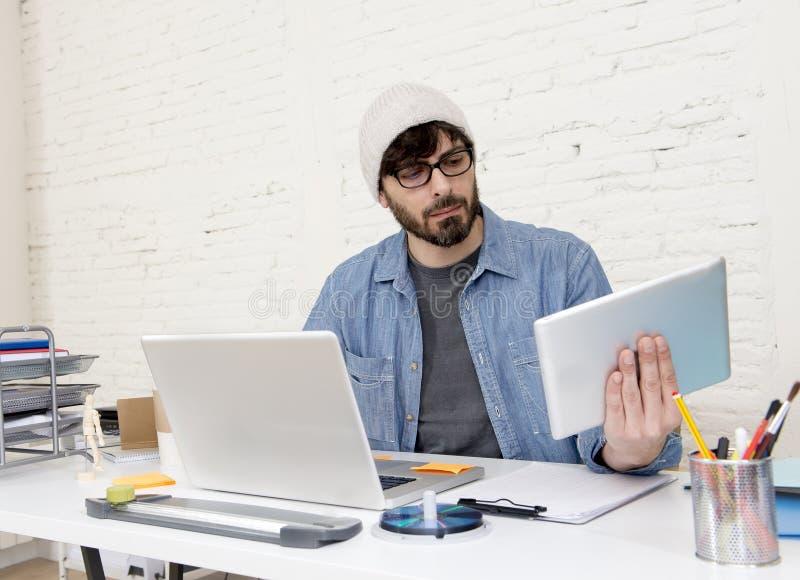 Молодой испанский привлекательный бизнесмен битника работая на современном домашнем офисе стоковые фото