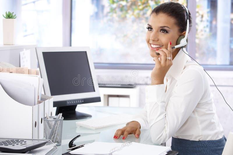 Молодой диспетчер работая в яркий усмехаться офиса стоковые фото