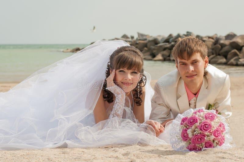 Молодой и красивый жених и невеста на пляже стоковые изображения rf
