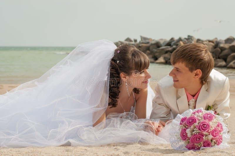 Молодой и красивый жених и невеста на пляже стоковое изображение rf