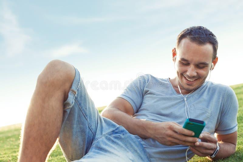 Молодой и красивый человек с передвижным smartphone стоковое изображение