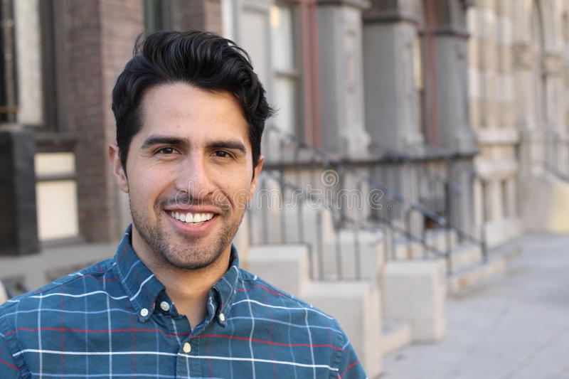Молодой и привлекательный мужчина латиноамериканца усмехаясь в городе стоковые изображения