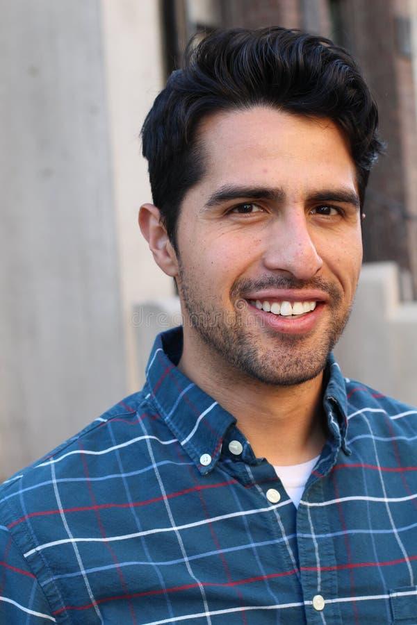 Молодой и привлекательный мужчина латиноамериканца усмехаясь в городе стоковое фото rf