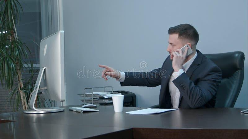Молодой кавказский бизнесмен вызывая с smartphone и говоря серьезно в офисе стоковые изображения rf