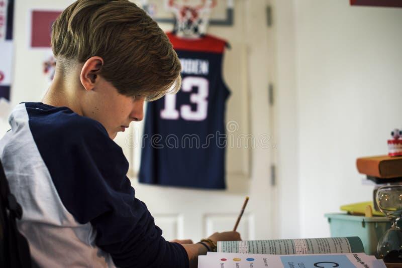 Молодой кавказский мальчик делая домашнюю работу стоковые фото