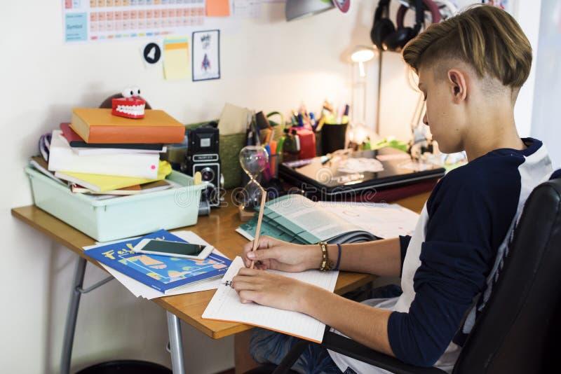 Молодой кавказский мальчик делая домашнюю работу стоковое фото