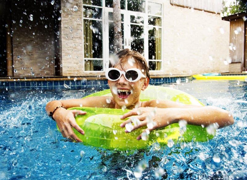 Молодой кавказский мальчик наслаждаясь плавать в бассейн с трубкой стоковое фото rf