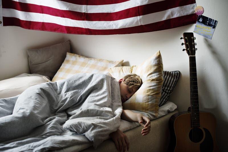 Молодой кавказский мальчик спать в кровати стоковая фотография rf