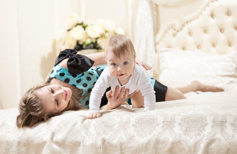Молодой кавказский сын матери и младенца на кровати стоковое изображение