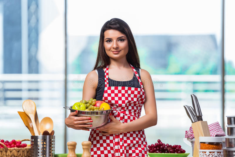 Молодой кашевар с плодоовощами в кухне стоковые изображения