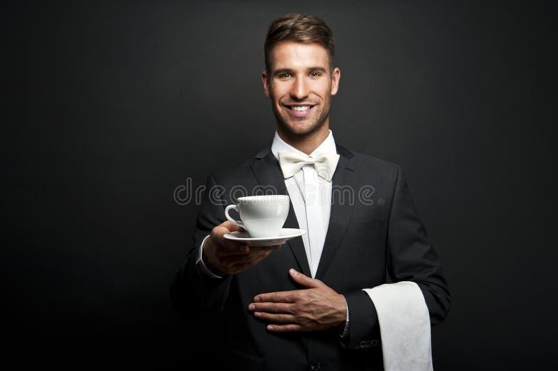 Молодой кельнер в кофе равномерной сервировки горячем стоковое фото rf