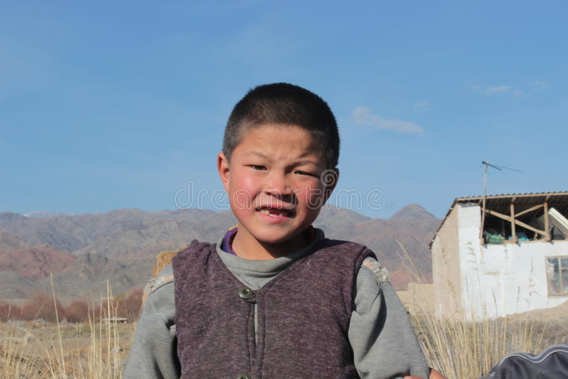 Молодой киргизский мальчик смотря в камеру стоковые фото