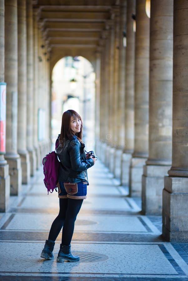 Молодой красивый азиатский женский путешественник стоя на улице внутри стоковое фото rf