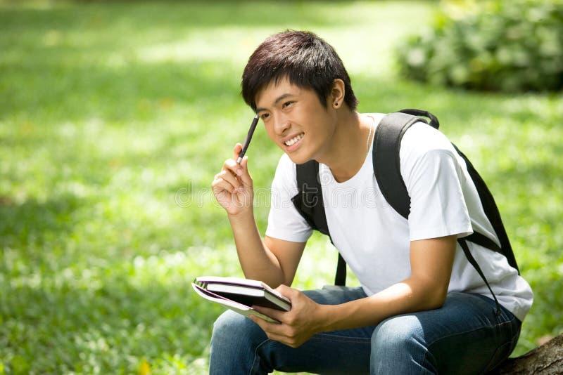 Молодой красивый азиатский студент с книгами и улыбкой в напольном стоковые фото