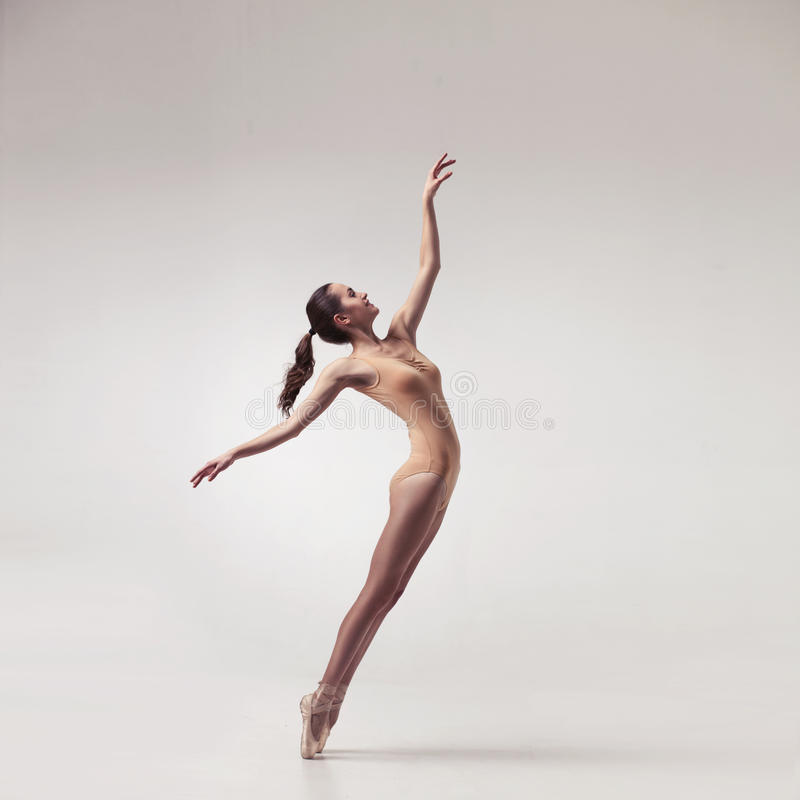Молодой красивый артист балета в бежевом купальнике стоковое изображение