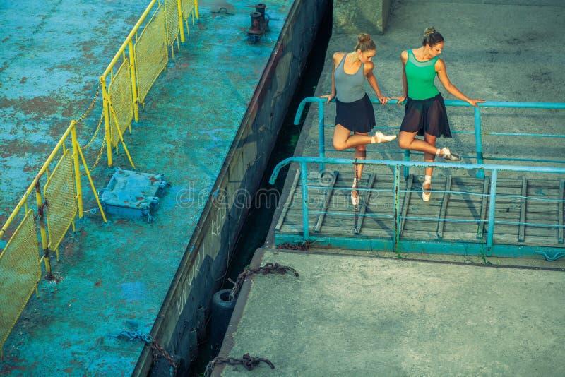Молодой красивый двойной балет танцев сестры 2 в городе с костюмом балета городской танец синхронизации промышленные танцы улицы  стоковое изображение rf