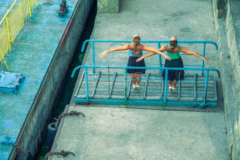 Молодой красивый двойной балет танцев сестры 2 в городе с костюмом балета городской танец синхронизации промышленные танцы улицы  стоковое фото rf