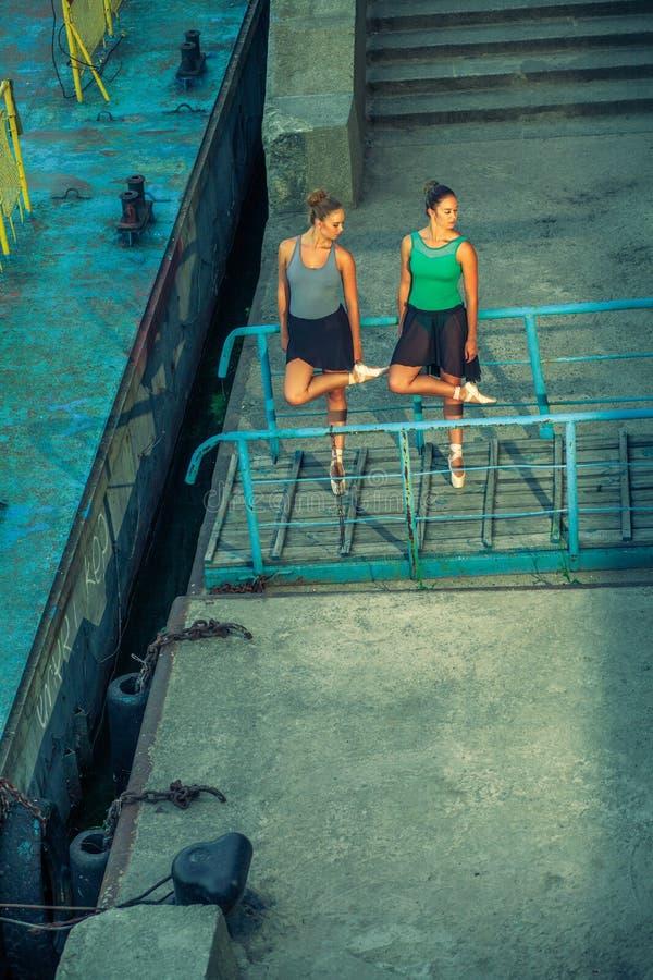 Молодой красивый двойной балет танцев сестры 2 в городе с костюмом балета городской танец синхронизации промышленные танцы улицы  стоковое изображение