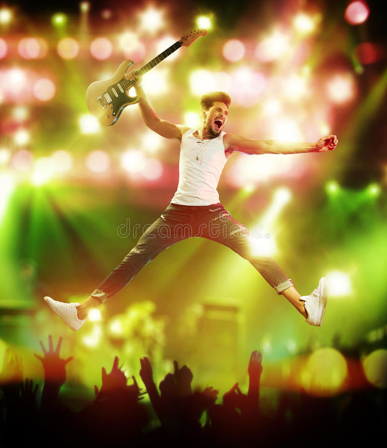 Молодой, красивый гитарист скача на этап стоковое изображение rf
