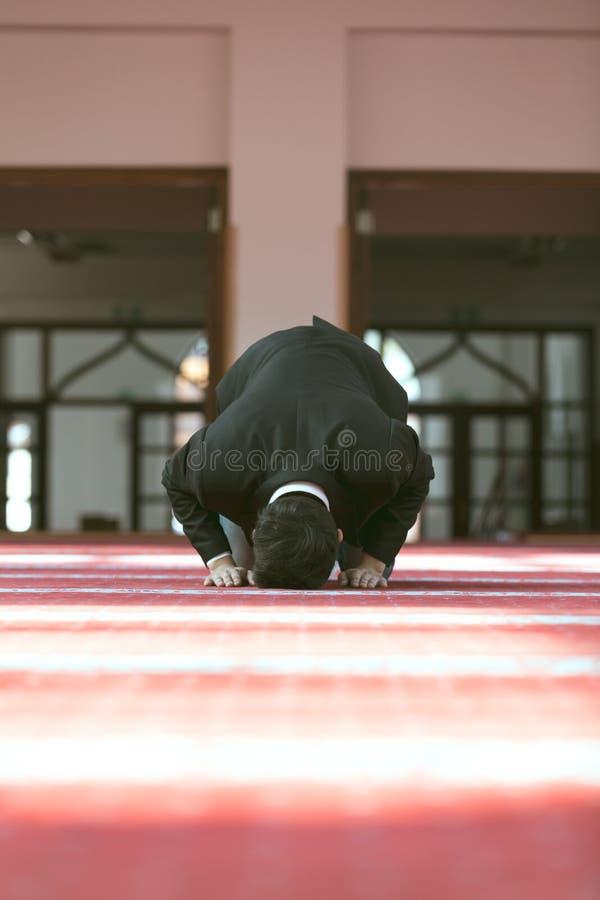 Молодой красивый мусульманский человек моля в мечети стоковое фото