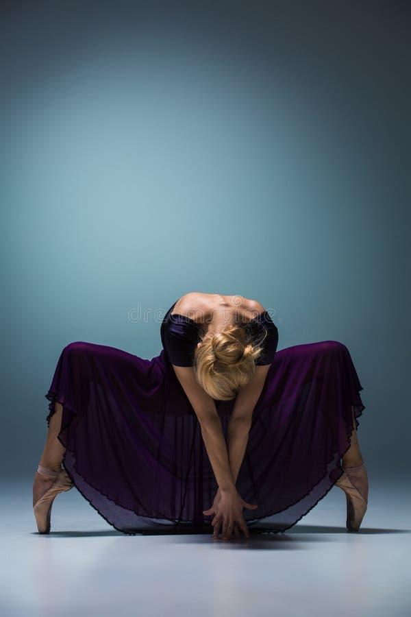 Молодой красивый современный танцор стиля представляя на предпосылке студии стоковое изображение rf