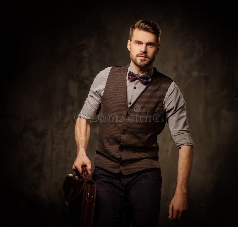 Молодой красивый старомодный человек при портфель представляя на темной предпосылке стоковое изображение