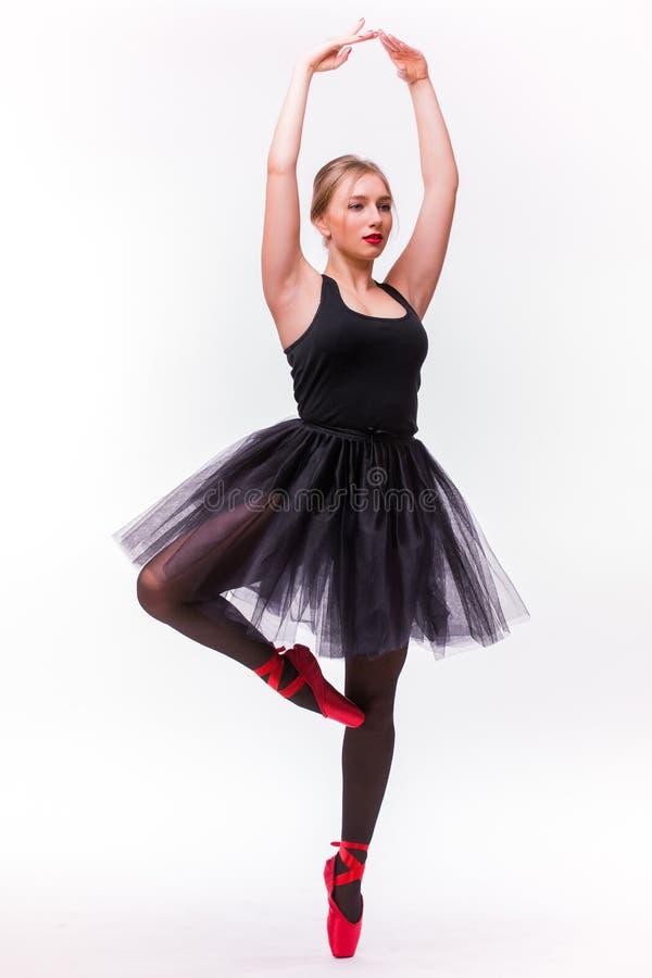 Молодой красивый танцор балерины представляя на предпосылке студии стоковое изображение