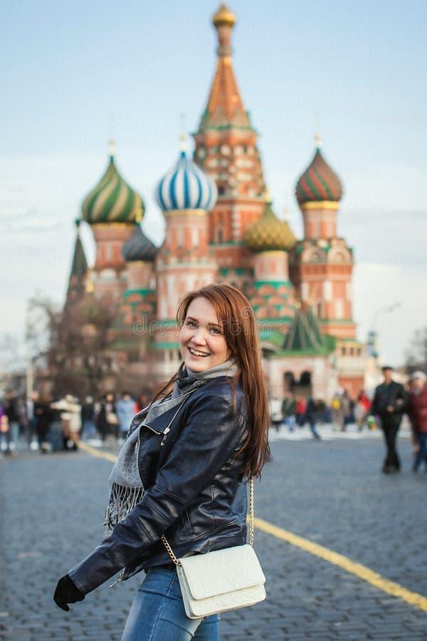 Молодой красивый турист женщины имея потеху на красной площади предпосылки, Москву Кремль, Россию стоковое фото