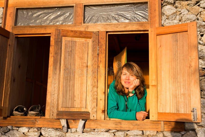Молодой красивый усмехаясь портрет окна счастливой женщины отдыхая стоковые фото