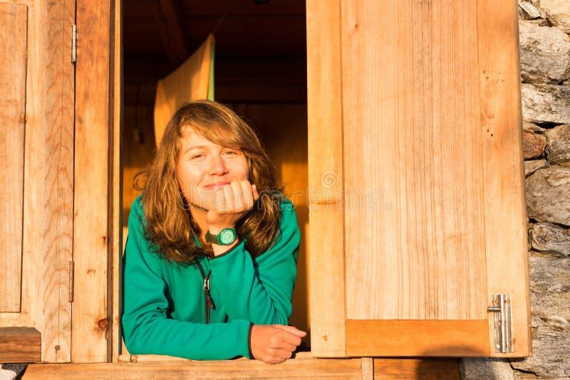 Молодой красивый усмехаясь портрет окна счастливой женщины отдыхая стоковые изображения